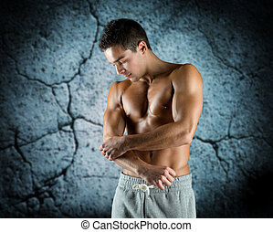 young male bodybuilder injured touching elbow - pain, sport,...