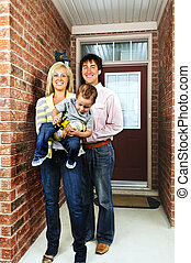 Happy family at home - Young happy family in front of house