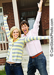 Excited couple at home - Young excited couple celebrating in...