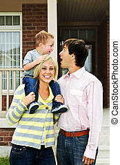 Happy family in front of home - Young happy family standing...