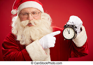 Pay attention to time - Smiling Santa pointing at alarm...