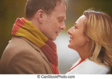 Romantic love - Faces of romantic couple looking at one...