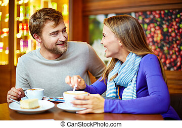 Teatime conversation - Young cheerful couple talking in cafe...