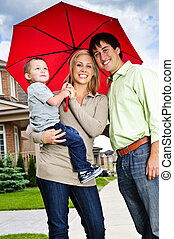 Happy family with umbrella - Young happy family under...