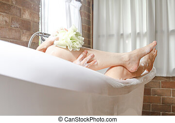 closeup leg women taking a shower in a bathtub