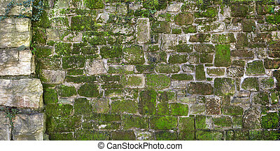 Mossy old natural stone wall - Panorama of an ancient,...