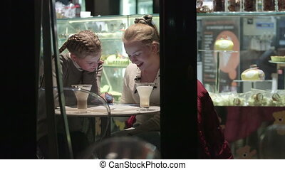 Look through night window at two girls conversation in cafe