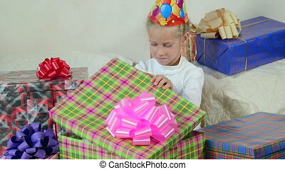 Child opening gift boxes sitting on bed in the room
