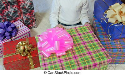 Little girl opening large gift box with white soft toy