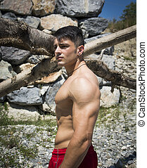 Muscular shirtless young man outdoor, thinking