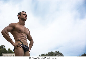 Handsome muscular young man in bathing suit shot from below