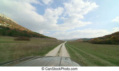 SUV driving on dirt road through the valley near Crimean...