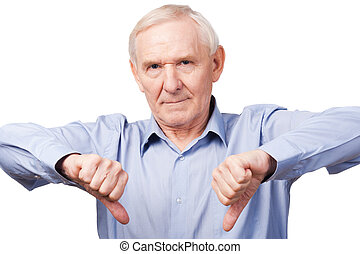 I said no! Serious senior man in shirt showing his thumbs down and looking at camera while standing against white background