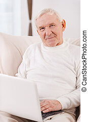 Surfing the net Confident senior man working on laptop and...