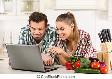 Kitchen - Young happy couple are looking for recipe Healthy...