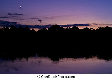 moonrise sunset - quarter moon at sunset over a lake