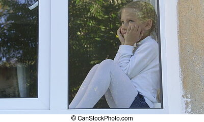 Cute little girl looking out window view from outside