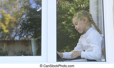 Cute little girl sitting by the window playing with digital...