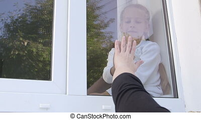 Little girl gives parting kiss to mother through window pane