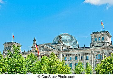 German Parliament with national flag in Berlin, Germany -...