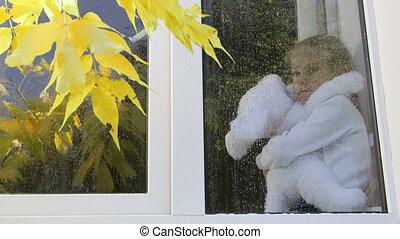 Child with toy looking out the window on a rainy autumn weather