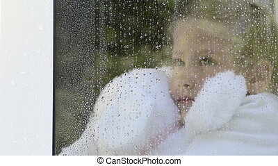 Little girl hugging stuffed toy looking out window in the rain
