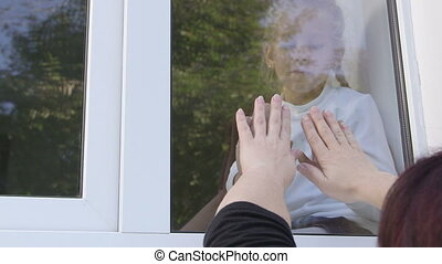 Mother and child looking at each other hands pressed against window glass
