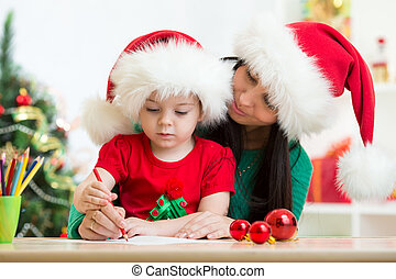 Child girl and mom writing christmas letter to Santa - child...