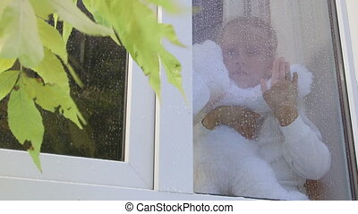 Pensive little girl looking out window pressing hand to the glass