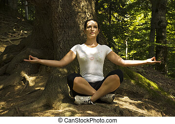 Woman doing  yoga in lotus position outdoors