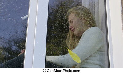 Teenage girl at window crying in the rain view from outside