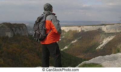 Hiking man standing on edge of plateau in Crimean mountains...