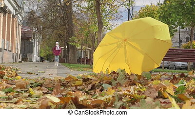 Yellow umbrella and golden fallen leaves on a sidewalk in...