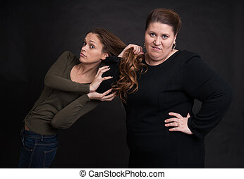 two angry women fighting over black background