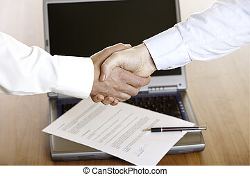 HANDSHAKE OF BUSINESSMAN AFTER SIGNING OF CONTRACT