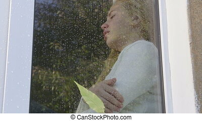 Sad crying little girl looking at mother through window pane parting