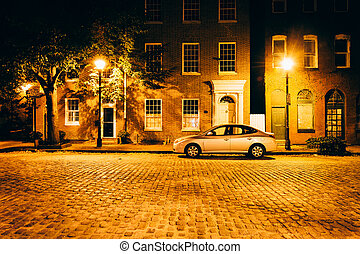 Parked car in front of brick buildings on a cobblestone street a