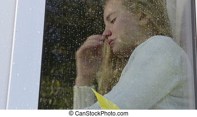 Crying girl sitting by window in the autumn rain close-up