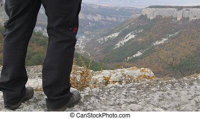 Hiking man standing on edge of Mangup plateau in Crimean...