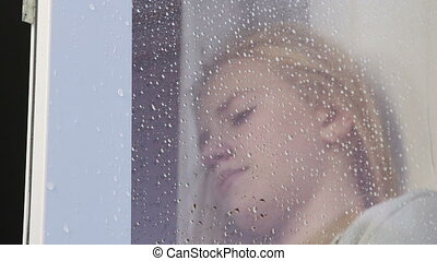Face of sad  teenage girl behind window glass with raindrops