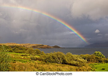 Wonderful rainbow above the lake with the cloudy sky, Isle...