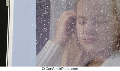 Sad teenage girl looking out window with rain drops close-up...