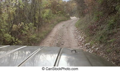 Off road driving on stony mountain track down slope