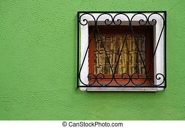 Green wall and small window, traditional house of Burano...