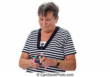 Brain teaser - Senior woman with rubik's cube - isolated on...