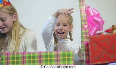 Children open up boxes with gifts close-up