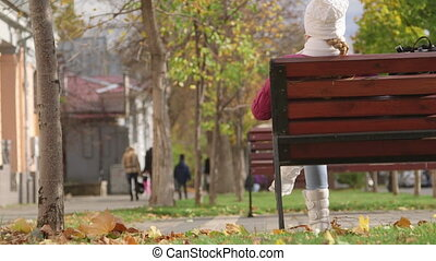 Girl sitting on bench in autumn
