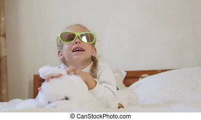Children wearing passive 3d glasses watching TV on the bed