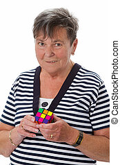 Problem solving - Senior woman with rubiks cube - isolated...