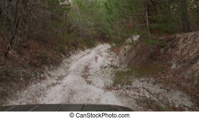 Off-road vehicle driving on rutted dirt road through the...